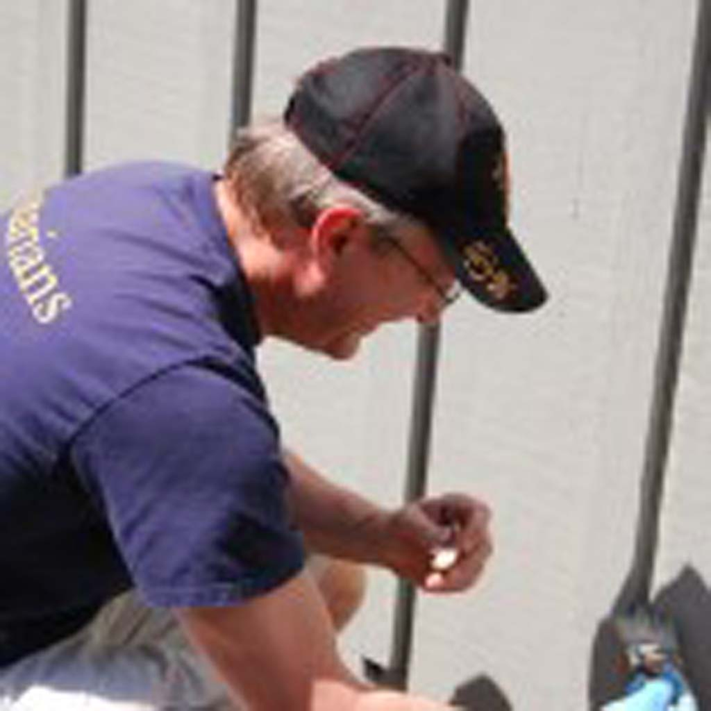 Rotarian Greg Grajek works on painting a shed. Photo by Tony Cagala