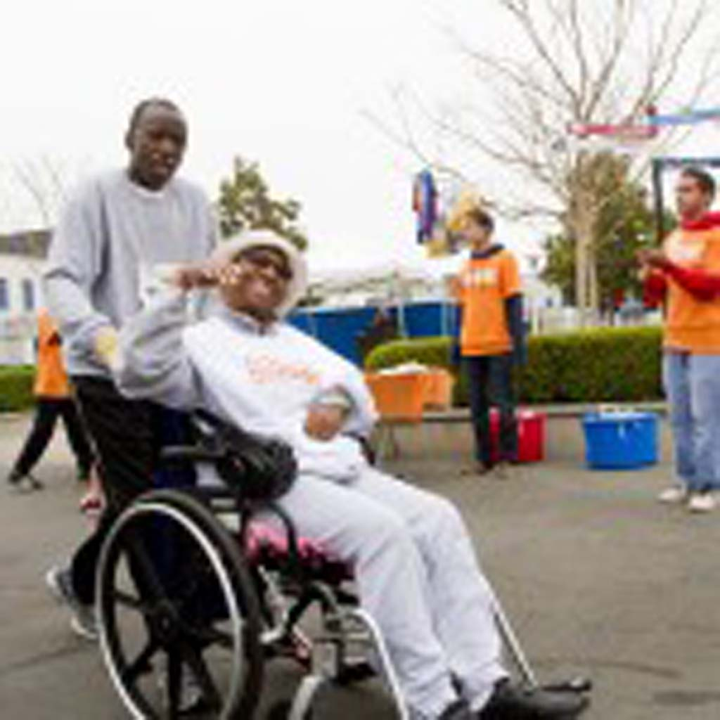 Glendora resident Mike Ward pushes his wife Charlie Ward past a group of cheering volunteers. Photo by Daniel Knighton