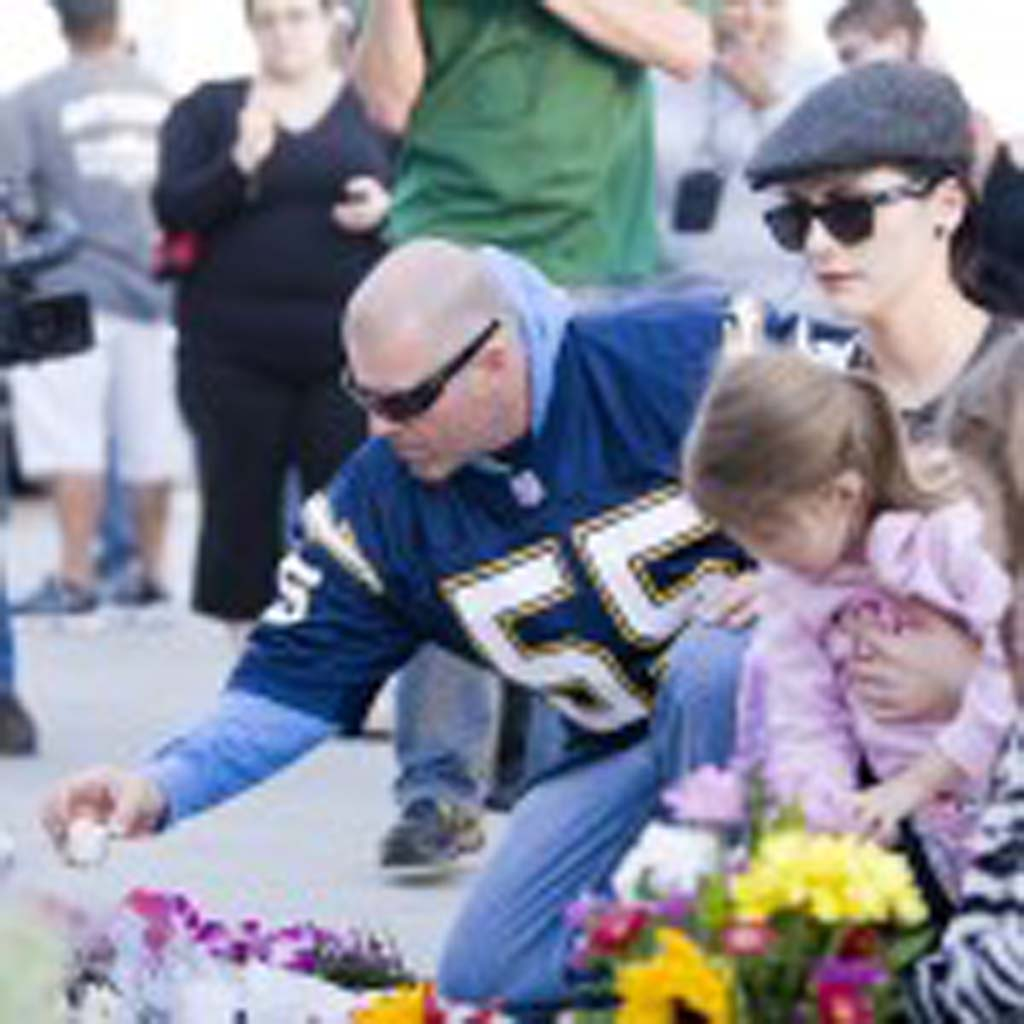 Wearing the No. 55 jersey of former San Diego Chargers all-pro linebacker Junior Seau, Vista resident Chris Vollmer places a lit candle on the makeshift memorial at Seau's beachfront home in Oceanside.  Photo by Daniel Knighton