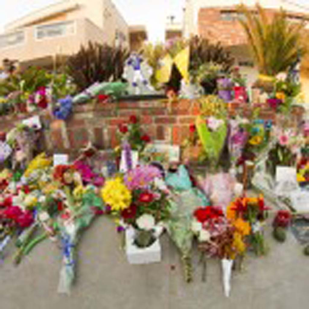 Fans, family and friends of Junior Seau gather to place flowers, hand written notes, and mementos in front of his beachfront home. Photo by Daniel Knighton
