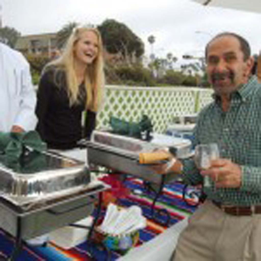 Del Mar resident Ben Giangiulio (right) a frequent customer at En Fuego Cantina & Grill, tries their tamales prepared and served at Summer Solstice by Alfredo Soto and Kelsey Gepner. Photo by Bianca Kaplanek