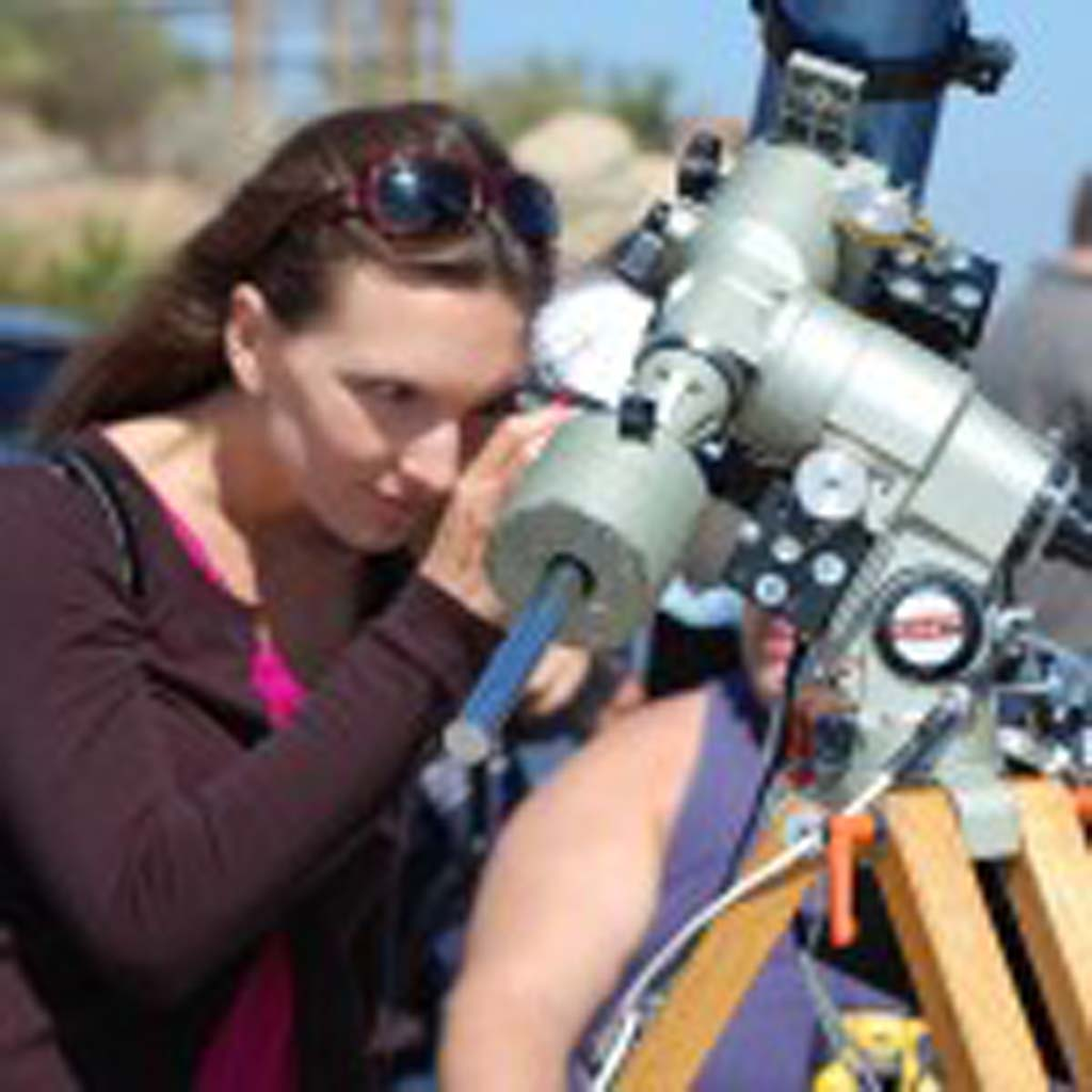 Danielle Mulcahy watches through a telescope the rare astronomical event Tuesday. Photo by Tony Cagala