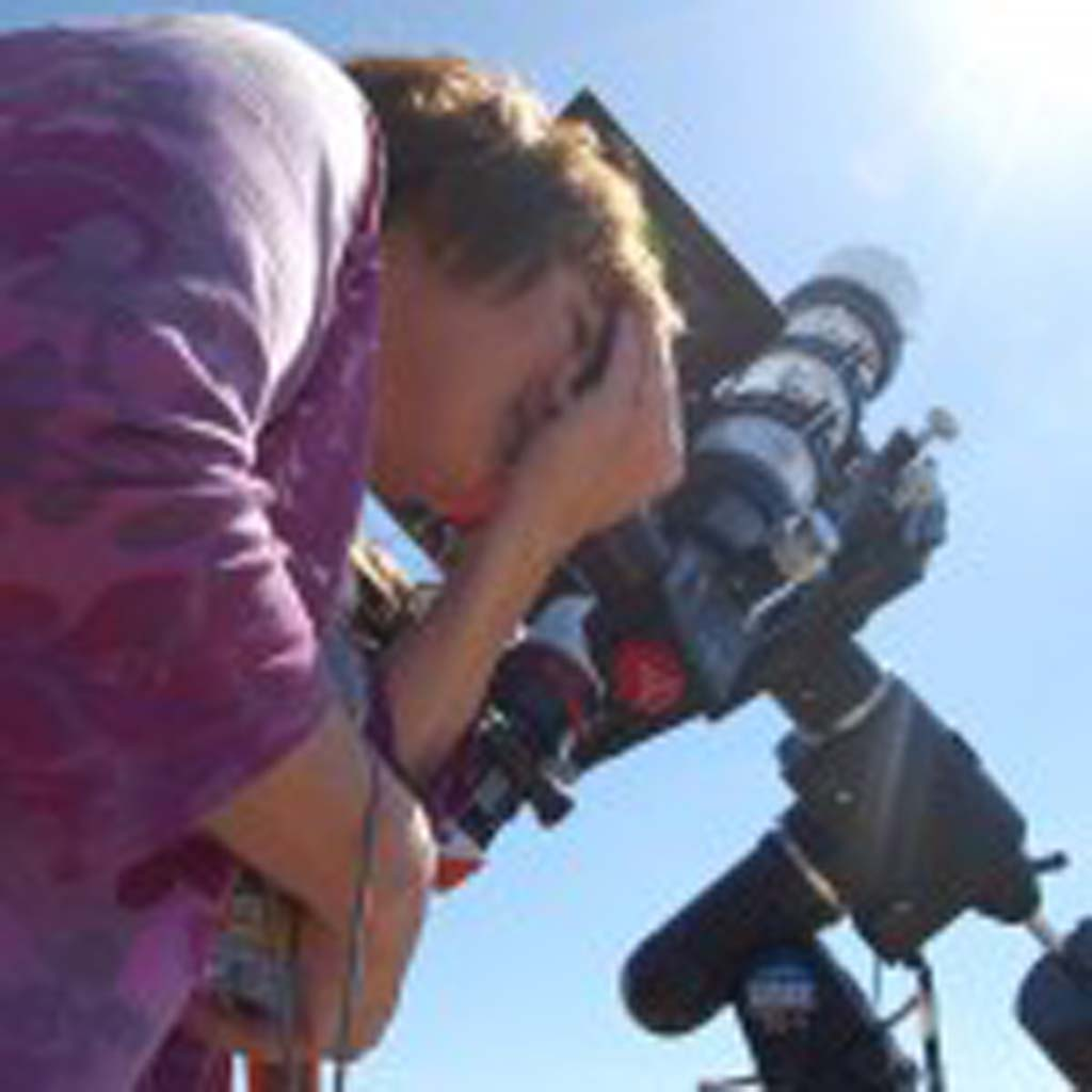 "Julia O'Riordan peers through one of the many telescopes on Double Peak Park to view the rare astronomical event. After seeing the planet arc across the sun she said, ""Whoo-hoo, this is cool."" Photo by Tony Cagala"