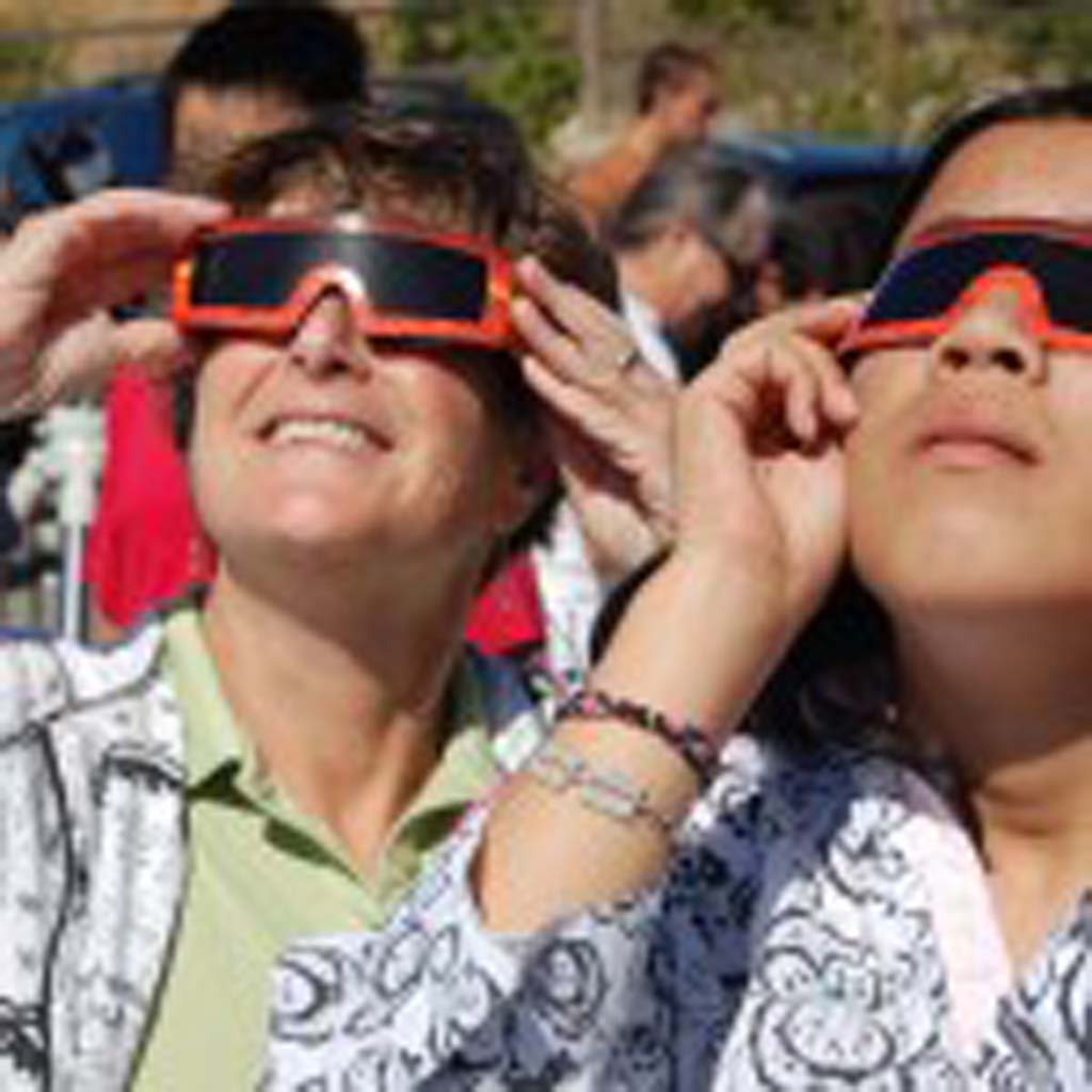 Merryl Goldberg (left) and her daughter Liana watch through solar glasses the Venus transit. Photo by Tony Cagala