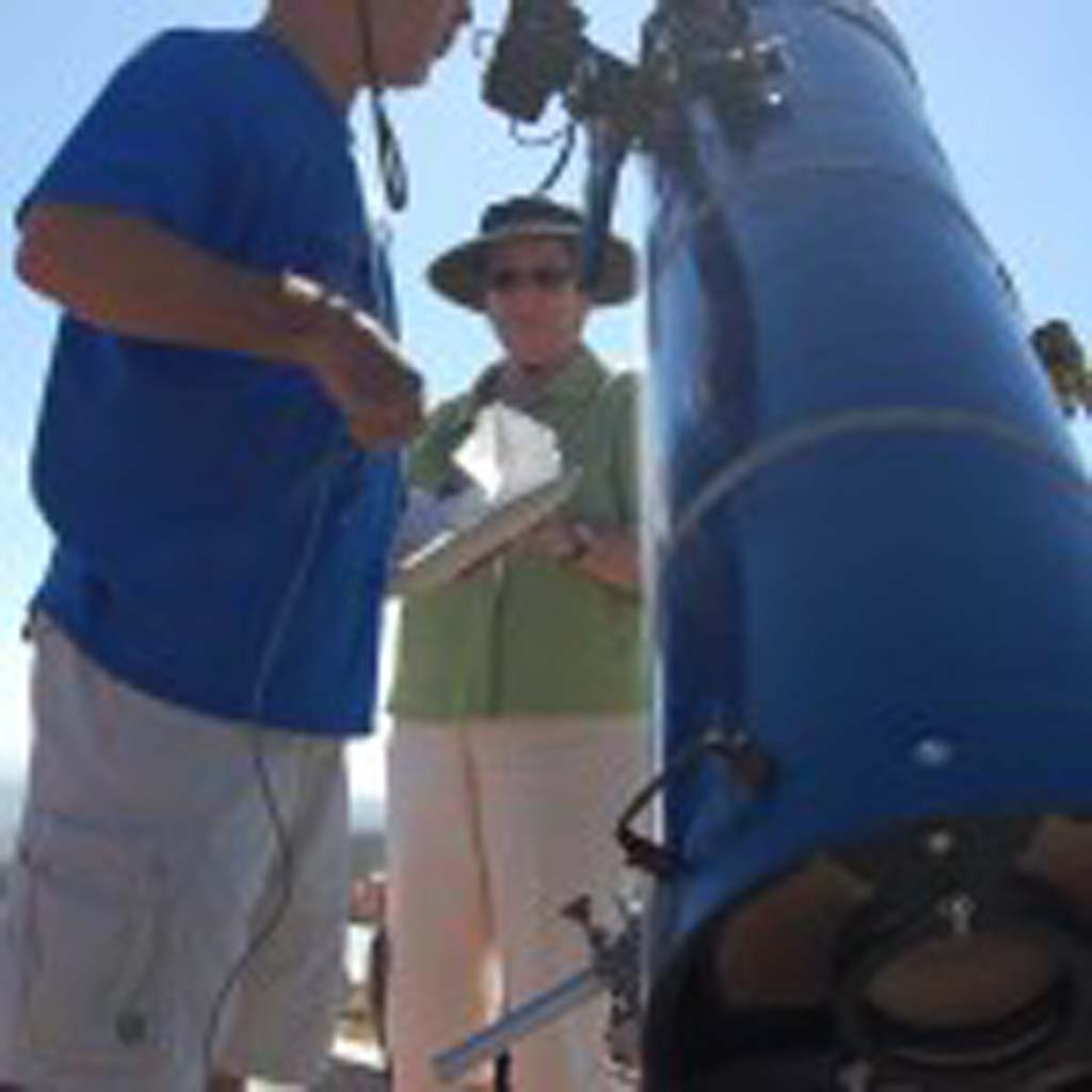 Tom Bartol (left) and his wife Wendy Graham stand by their telescope aimed at the Venus transit. Photo by Tony Cagala