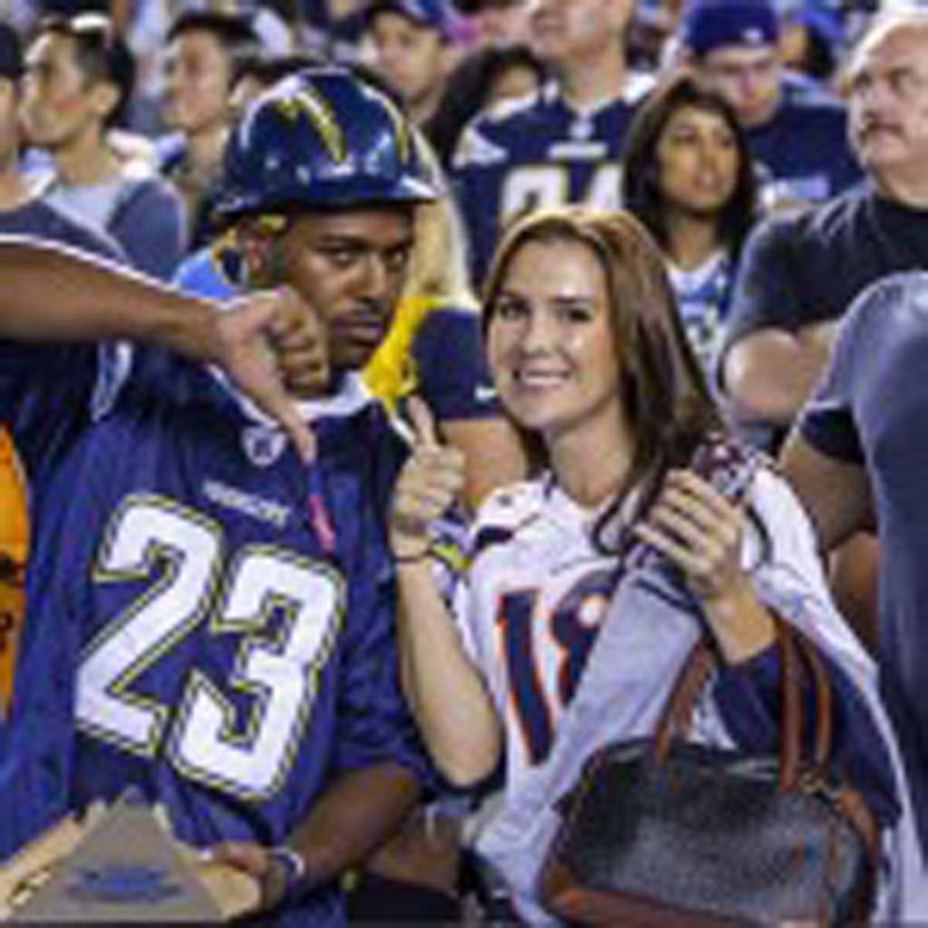 A Chargers fan can feel a shift in momentum following the second half when the Broncos came out with a scoring drive. A Denver fan is all smiles. Photo by Bill Reilly