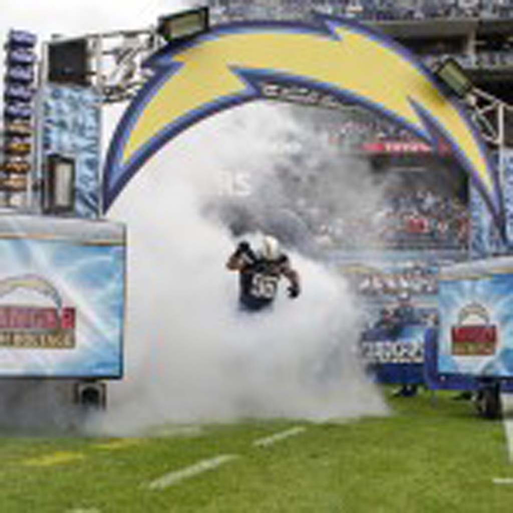 Chargers line backer Jarret Johnson emerges from the smoke during pre-game introductions. Photo by Bill Reilly