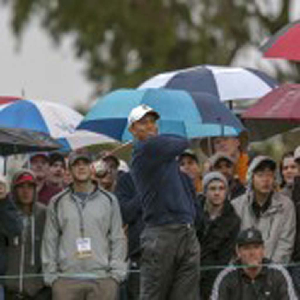 Tiger Woods drives through the rain at Torrey Pines. With a 7-under round of 65, Woods is at the top of the leader board at 11-under after day two at the Farmers Insurance Open. Photo by Bill Reilly