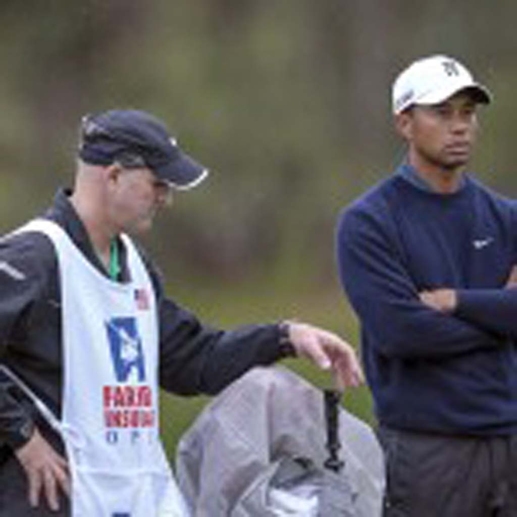 Tiger Woods stands in the rain waiting for his next shot with caddy Joe LaCava. Photo by Bill Reilly