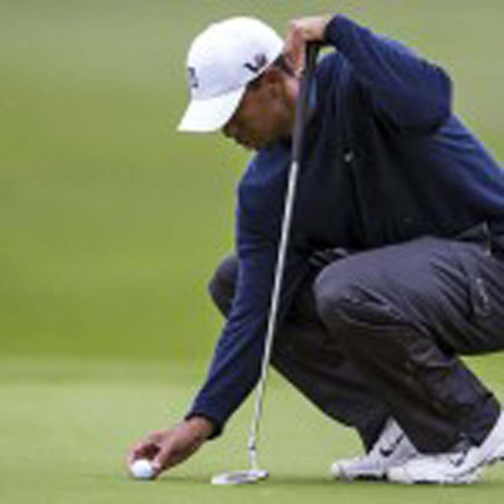 Tiger Woods marks his ball on the green. Photo by Bill Reilly