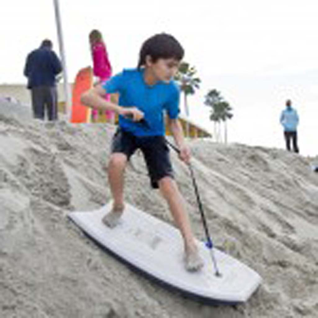 Spencer Lafferty, 10, sand-surfs in front of the lifeguard tower while waiting for the Penguin Plunge to start.