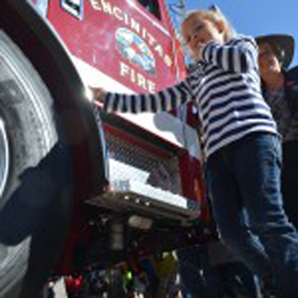 "6-year-old Mackenzie Jurchenko, whose grandfather is a retired firefighter, helps Deputy Mayor Lisa Shaffer and others in the fire house tradition of the ""pushing of the rig"" into the station following the grand opening ceremony. Photo by Tony Cagala"