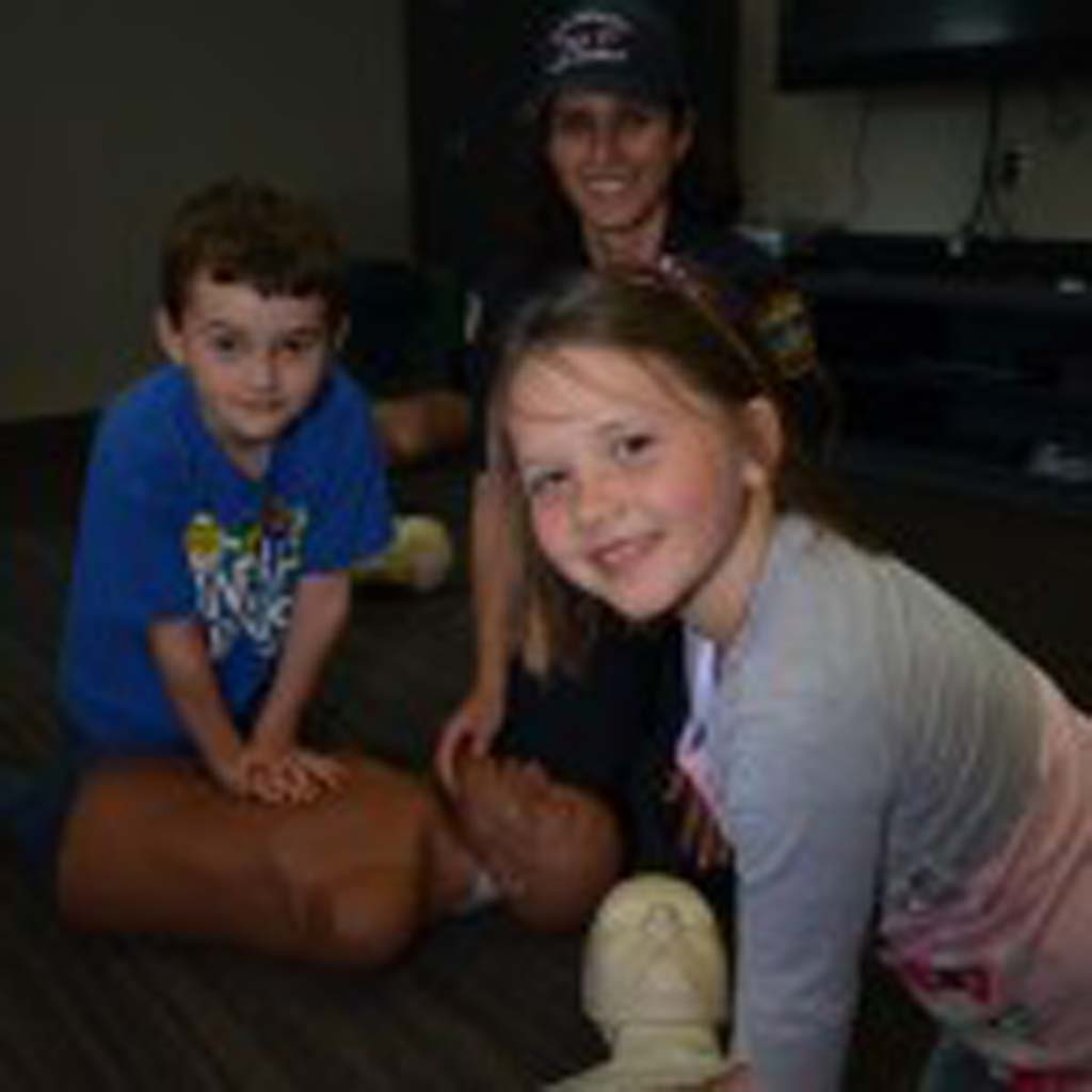 7-year-old Alex Baxter (left) and Mila Ellis, 7, get some CPR training from EMT Loralee Olejnik. Photo by Tony Cagala