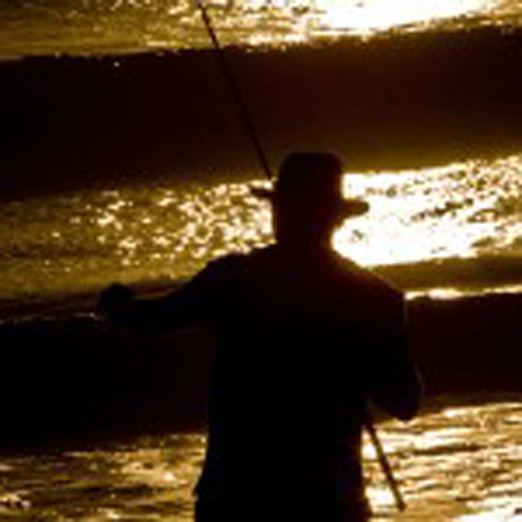 Victorville resident Mike Gehl is silhouetted against the setting sun as he fishes  at Swami's beach. Photo by Daniel Knighton