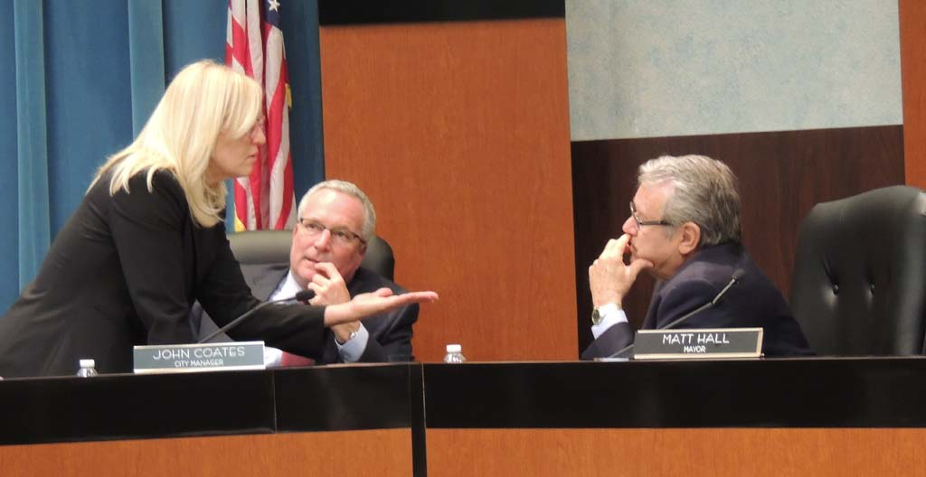 From left to right: Carlsbad City Attorney Celia Brewer, City Manager John Coates, and Mayor Matt Hall have a discussion during a break at the March 26 City Council meeting. The Council postponed any ruling on the Quarry Creek development project. Photo by Rachel Stine
