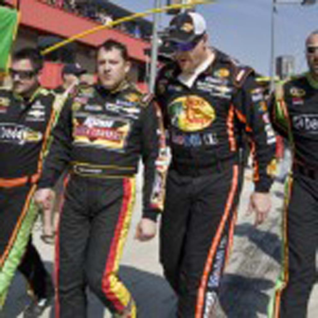 A very angry Tony Stewart (second from left) is escorted from the pits after a post-race altercation with Joey Logano. Photo by Daniel Knighton