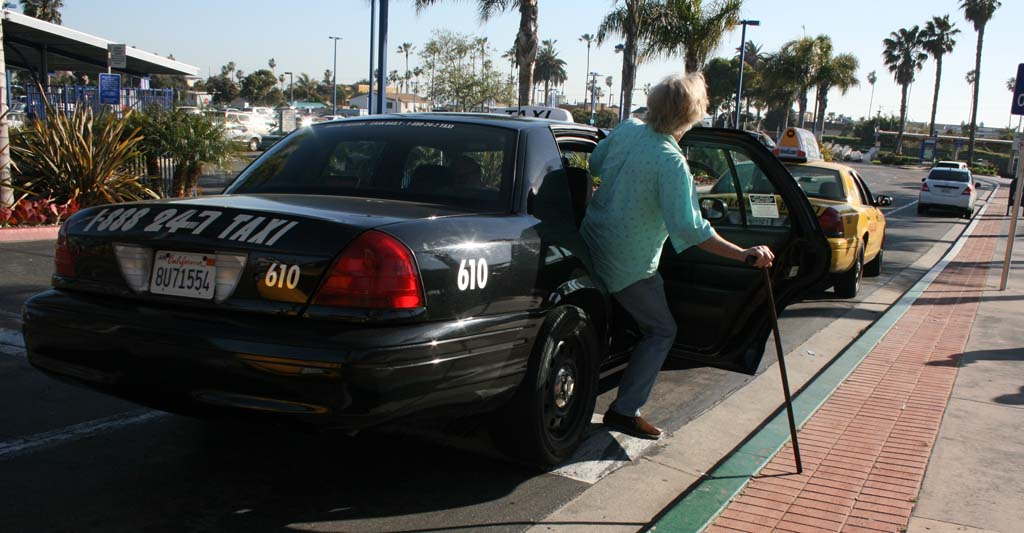 Oceanside senior Greg Smith boards a taxi driven by Donnie Aldridge. Aldridge said the taxi script program gives seniors more freedom. Photo by Promise Yee