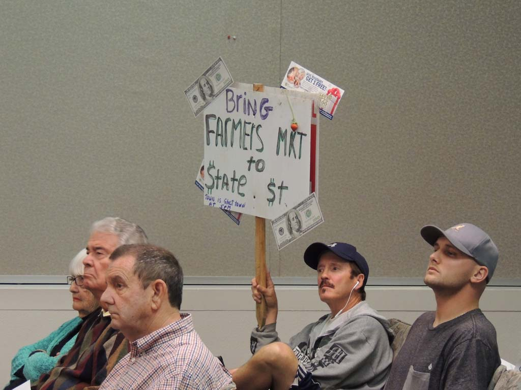"""Carlsbad resident and business owner Jim Clark holds a sign at the May 15 Planning Commission meeting in support of relocating the city farmers market to State Street. """"This will liven up this dead city,"""" he said during public comments. Photo by Rachel Stine"""