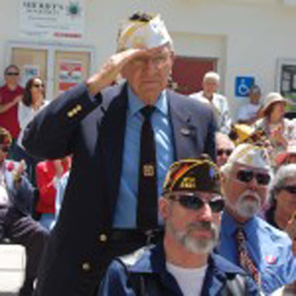 """VFW Post 5431 Chaplain Clarence Bytof stands as """"The Marines' Hymn"""" is played by the Santa Fe Christian High School band. Photo by Bianca Kaplanek"""
