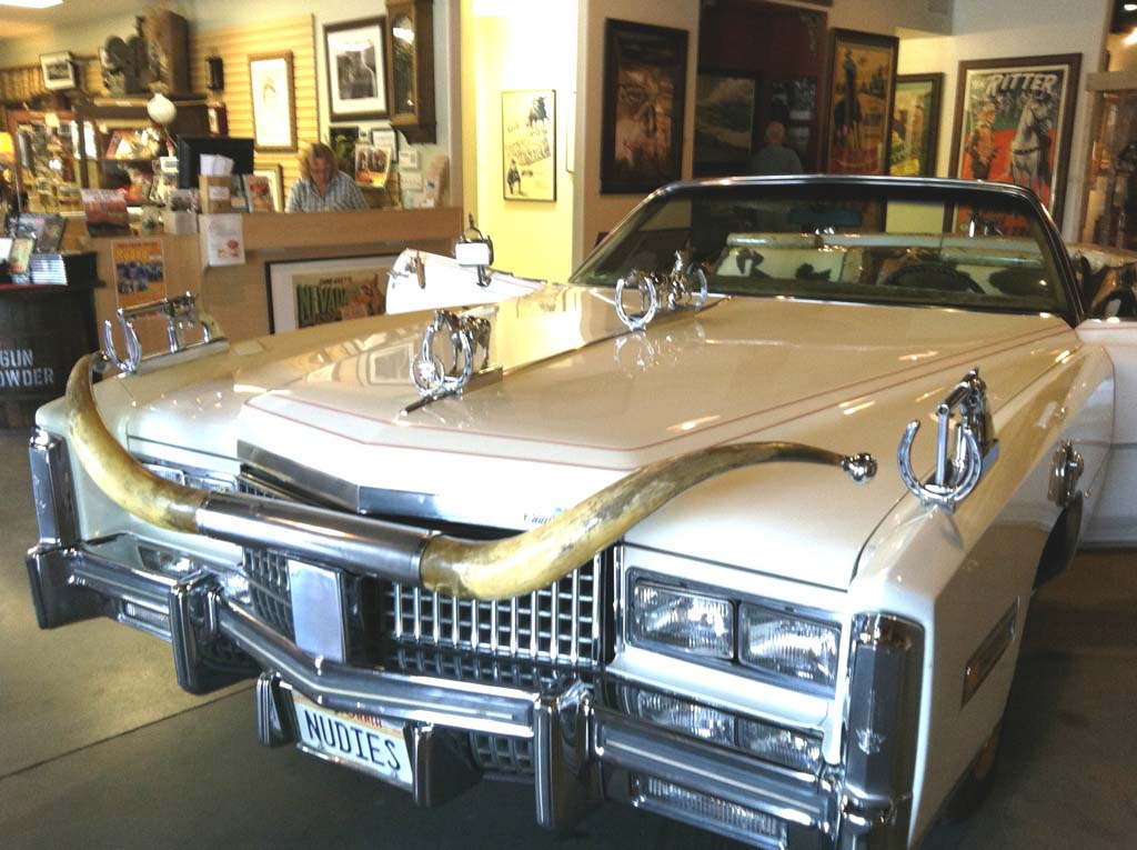 """This 1975 Cadillac Eldorado at the Lone Pine Film History Museum once belonged to Nudie Cohn (1902–1984), a Ukrainian-American tailor who designed outrageous """"Nudie Suits"""" for celebrities. Among his creations were a gold lame jumpsuit for Elvis and a star-studded, 10-gallon hat for Elton John. His auto collection of 18 cars was as outrageous as his couture. It included mostly white Pontiac Bonneville convertibles with silver-dollar-studded dashboards, pistol door handles and gearshifts, extended rear bumpers and enormous longhorn steer hood ornaments. Photo by E'Louise Ondash"""