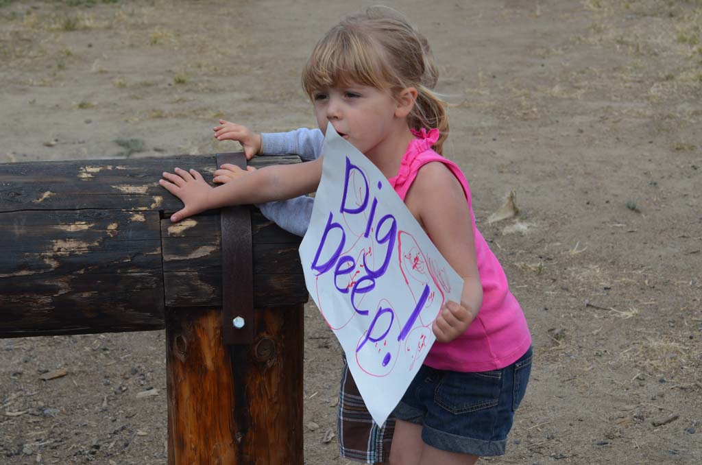 "A young girl encourages her dad to ""Dig Deep"" during the Recon Challenge. Photo by Jared Whitlock"