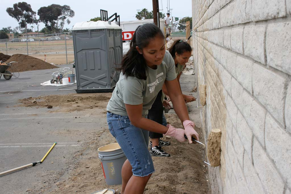 """North Coast Church volunteers Ana Kieffer (front) and Kristina Titopace take on painting a 150 by 10 foot wall at Oceanside Boys and Girls Club during the weekend of service. Project manager Kevin Rentz said volunteers were in good spirits. """"We accomplished all the tasks we set out to accomplish."""""""