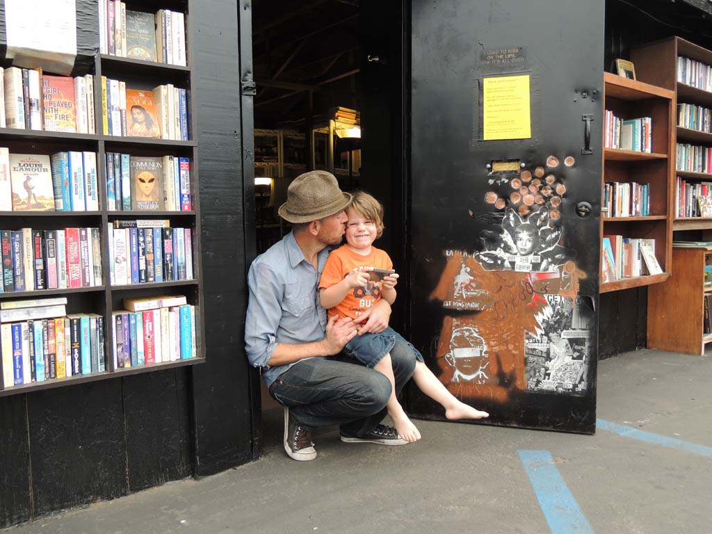 Sean Christopher holds his 4-year-old son, Jack, outside of the free bookstand he set up outside of his bookstore, L.H.O.O.Q. Books, in Carlsbad Village. Photo by Rachel Stine