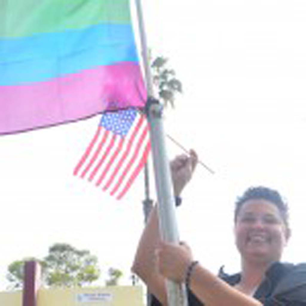 Michelle Coccari, a volunteer with the North County LGBTQ Resource Center adorns a rainbow flag with an American flag outside of the center on Wednesday, following the U.S. Supreme Court's rulings on same-sex issues. Photo by Tony Cagala