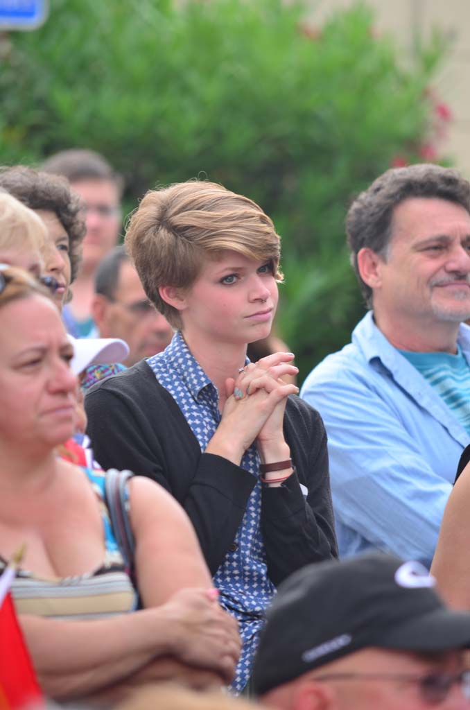 Cassidy Purdy, a member of Pilgrim United Church of Christ in Carlsbad listens to a speaker at a celebration out front of the North County LGBTQ Resource Center. Photo by Tony Cagala