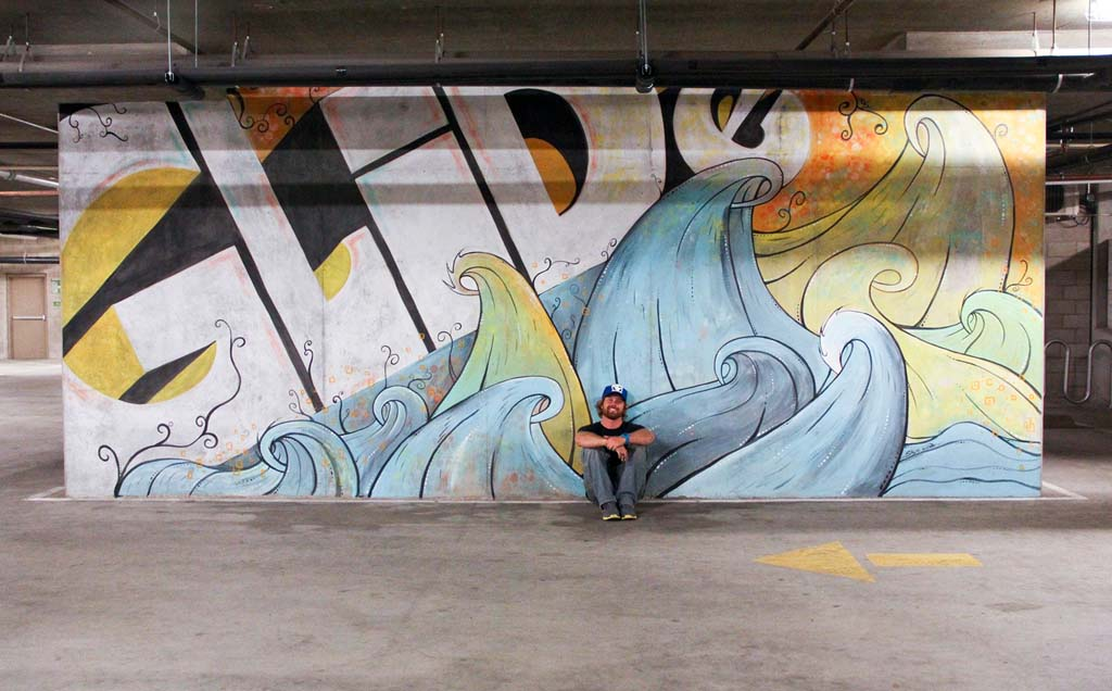 """Artist Skye Walker with his 24-foot """"Glide"""" mural at Whole Foods in Encinitas. (Courtesy photo.)"""