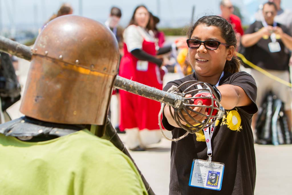 San Diego resident Jasmin Garcia gets a chance to practice medieval combat with an armored member of the Society for Creative Anachronism during the annual Comic-Con International convention in San Diego. Photo by Daniel Knighton