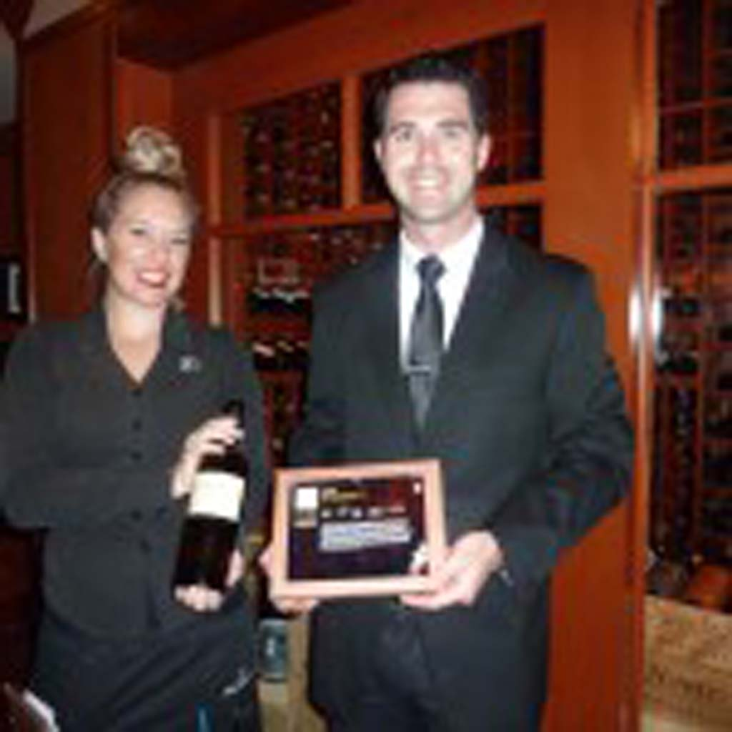 Ashlee Cote, left, table server and Casey Eades, operating partner for Fleming's La Jolla, demonstrate the new WiNEPAD with a bottle of Ladera Howell Mt. 2008 Cabernet. Photo by Frank Mangio
