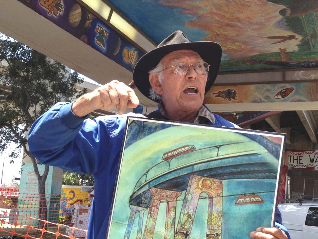 "Muralist and community activist Savador Torres shows off a sketch of his vision for the San Diego-Coronado Bay Bridge, which he envisions as an extension of the murals in Chicano Park in Barrio Logan. Known locally as ""the architect of the dream,"" the artist painted many of the murals during the 1970s, and was instrumental in recently refurbishing them. Born in El Paso, Texas, Torres grew up in Barrio Logan; his family home once stood where the park stands today. [Photo by Laurie Brindle]"