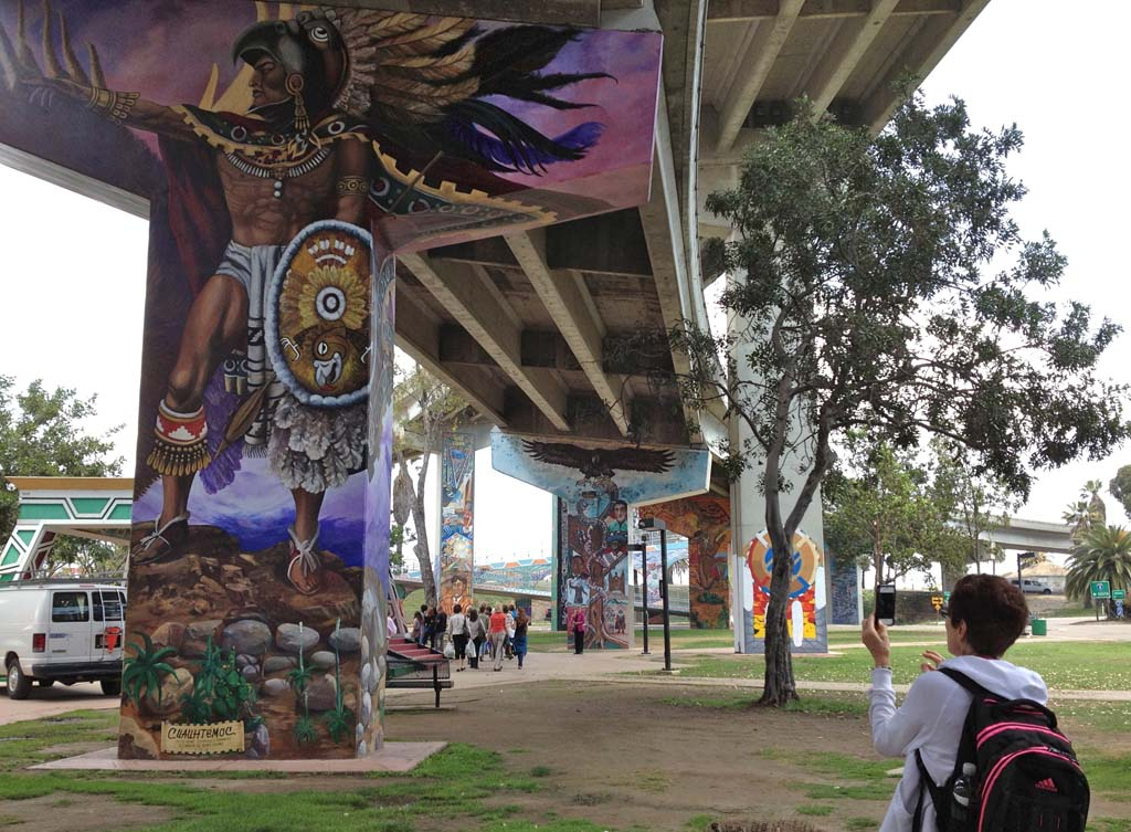 Chicano Park, created under the east-west approach ramps of the San Diego-Coronado Bay Bridge, is home to more than 50 murals that were painted mostly from 1973 to 1989. Earlier this year, and after many years of advocacy, the murals were placed on the National Register of Historic Places. Chicano Park took shape after a few hundred community residents stood up to bulldozers in April 1970. The state wanted to build a California Highway Patrol substation, but the city had previously promised the land for a neighborhood park. The murals draw people from the world over. [Photo by Laurie Brindle]