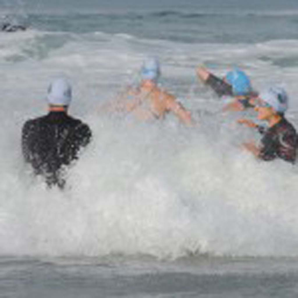Several women make their way through the waves in the 1K ocean swim, first event of the Carlsbad Triathlon. Photo by Rachel Stine