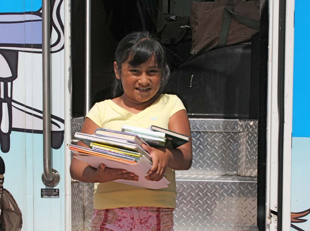 Leslie Garcia, 7, of Oceanside, checks out an armful of books. The Adelante Bookmobile will serve an estimated 10,000 people a year. Oceanside will add a second bookmobile and three more stops to its outreach service. Photo by Promise Yee