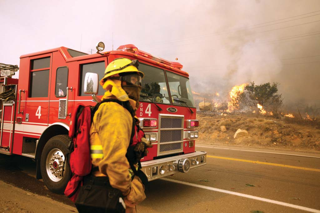 Scott Eugene from San Diego Fire Engine No. 4 accesses the situation during the Witch Creek fire in 2007. Fire fees intended to finance fire prevention services carried out by Cal Fire have resumed billing. File photo by Todd LeVeck