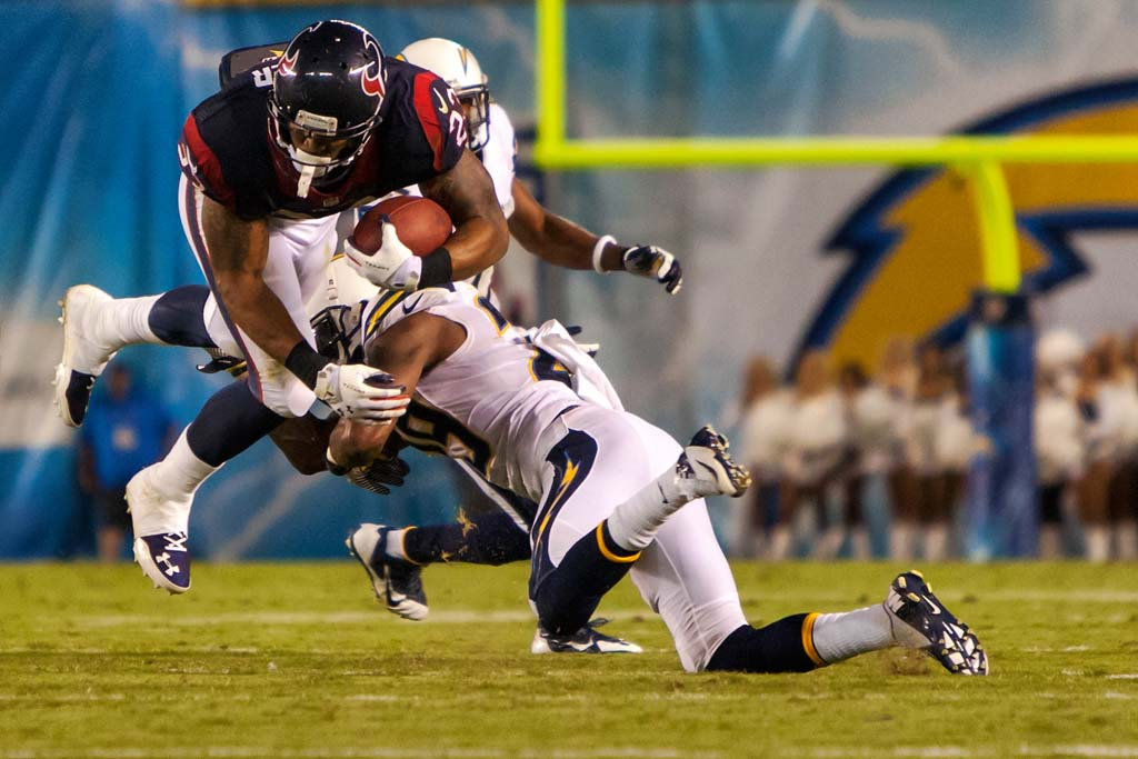 Houston Texans running back Arian Foster (23) is tackled by San Diego Chargers cornerback Shareece Wright. Photo by Bill Reilly