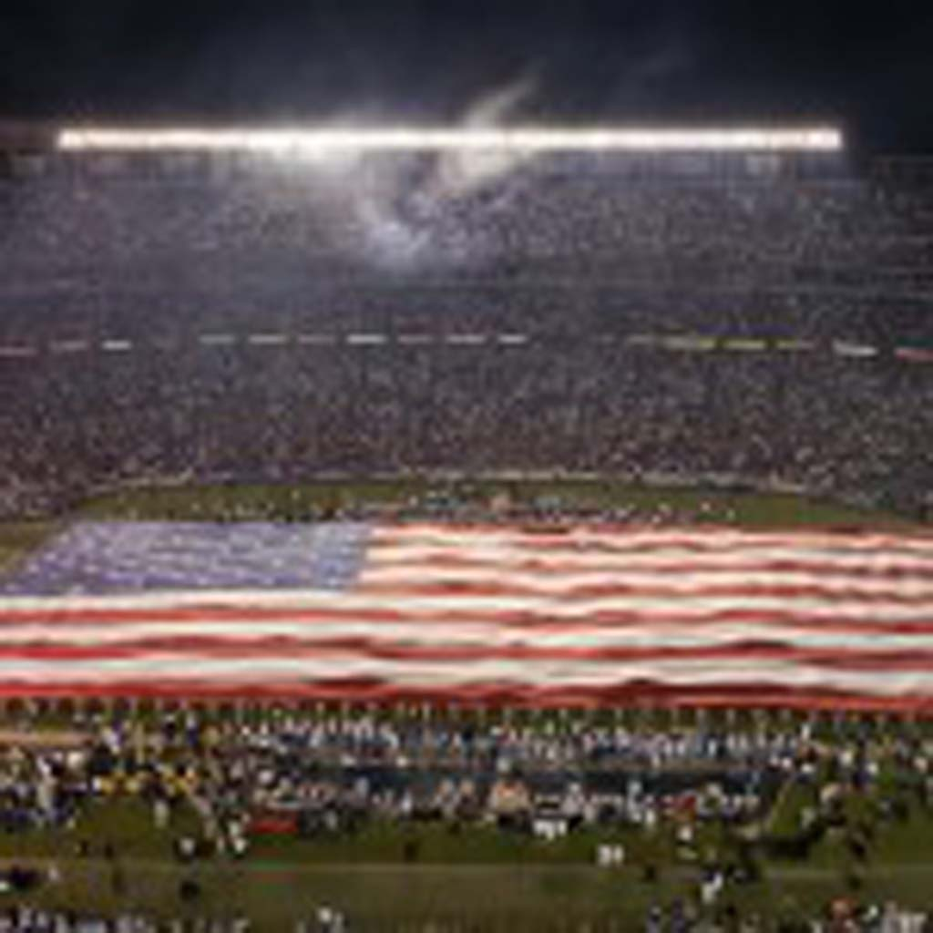 The United States Flag is spread out across the field during pre-game activities. Photo by Bill Reilly