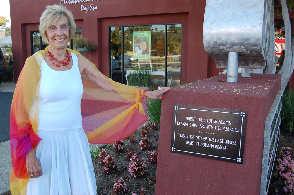 Nadine Frymann shows off a plaque she had installed on her property, Plaza 101 Center, to honor late architect Steve Adams. Photo by Bianca Kaplanek