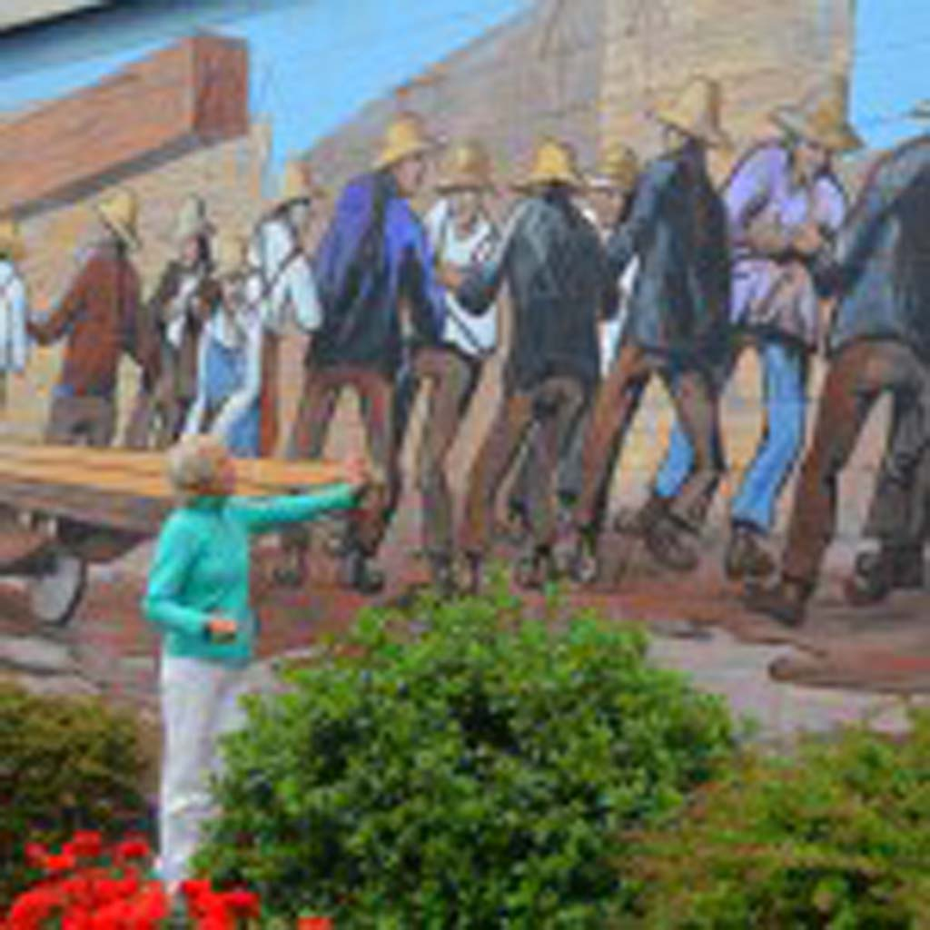 "Cim MacDonald explains the restoration process she used on this mural, originally painted in 1984 by Victoria artist Ernest Marza. The work depicts 23 men of the Chinese ""Bull Gang,"" who are struggling to move a huge timber through the Chemainus lumber yard. Their destination is a waiting ship in the harbor. Photos courtesy of Jerry Ondash"
