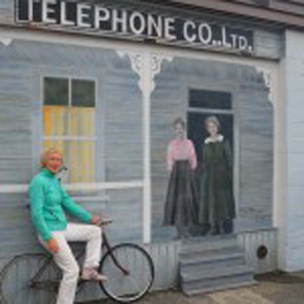 """The Telephone Company,"" was painted in 1992 by Cim MacDonald, perched on the antique bicycle, which is part of the artwork. The artists who also serves as curator of the 40-plus murals. The house, which still stands on Maple Street, was the town's first telephone exchange. ""There was only one telephone in town,"" explained MacDonald, ""so when a call came in, the operator would get on her bicycle and peddle to the person who was being called."""