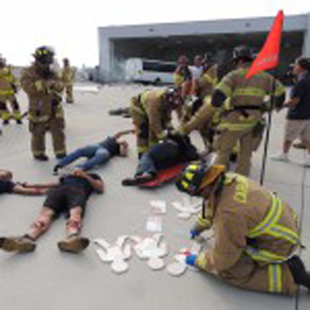 Fire fighters tend to volunteers with fake injuries during a mass casualty exercise just off the runway at McClellan-Palomar Airport.