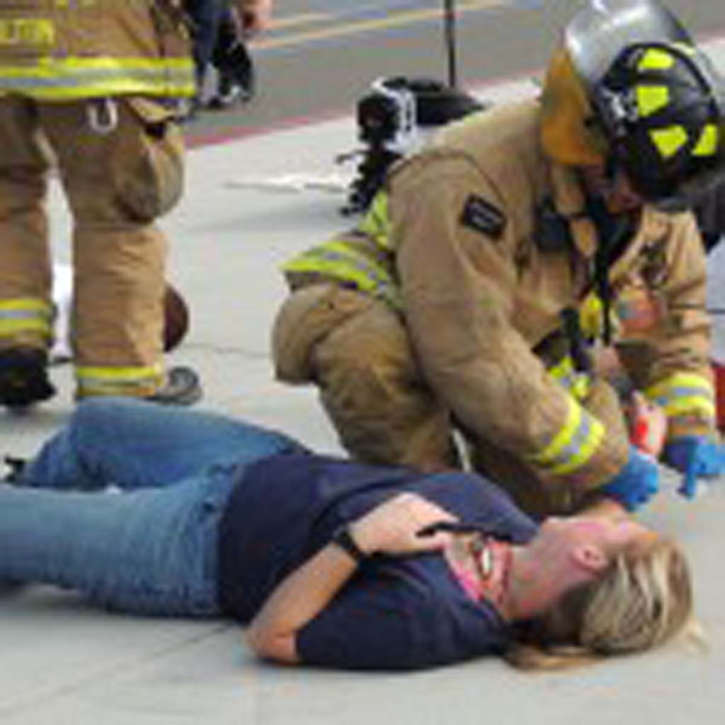 A fire fighter adds a wristband to a volunteer victim during the drill as she pleads for help.