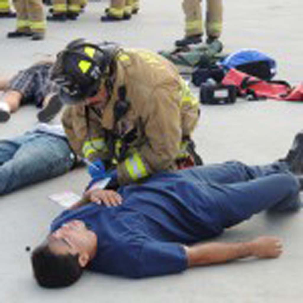 A Carlsbad fire fighter takes down the name of a pretend victim on an emergency identity card.