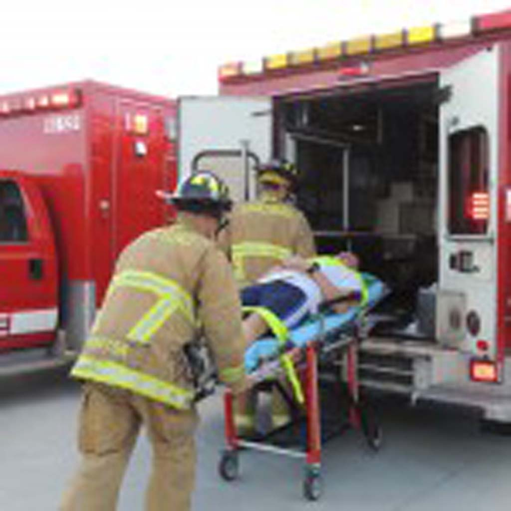 Carlsbad fire fighters load a volunteer victim into an ambulance.