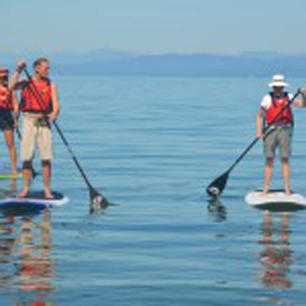 """Michael Addiscott, second from left, offers advice to a novice paddleboarder just off Qualicum Beach. Addiscott, a guide for Outsider Adventures Inc., moved from his native Scotland to the Canadian Riviera because of the proximity and convenience of outdoor activities in the area. """"You can do everything or nothing,"""" he tells visitors."""