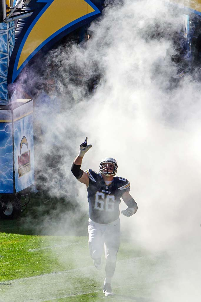 Chargers guard Jeromey Clary emerges from the smoke during pregame introductions. Photo by Bill Reilly