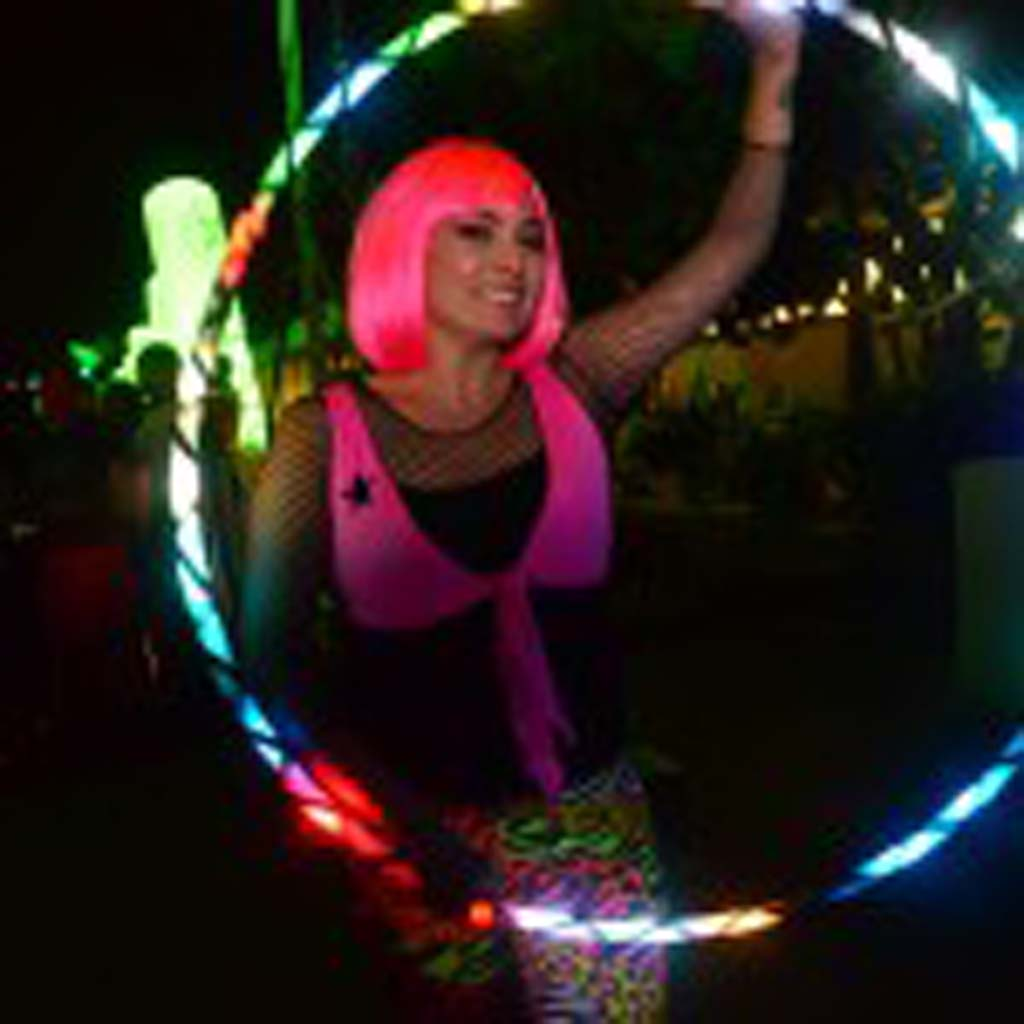 A glow dancer poses with her electric hula-hoop.