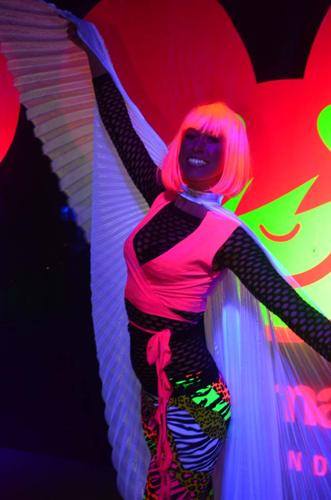 """A glow """"angel"""" poses near the finish line of the Electric Run race."""